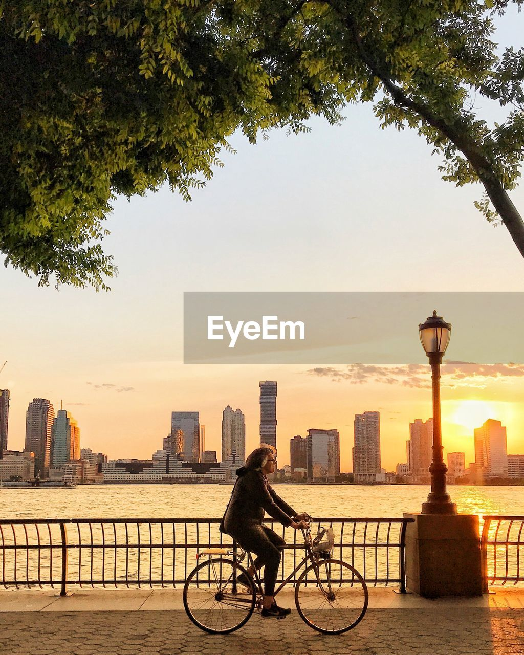 architecture, built structure, sky, city, building exterior, bicycle, nature, tree, sunset, transportation, one person, plant, street, mode of transportation, water, railing, building, land vehicle, real people, lifestyles, riding, outdoors, bridge - man made structure, office building exterior