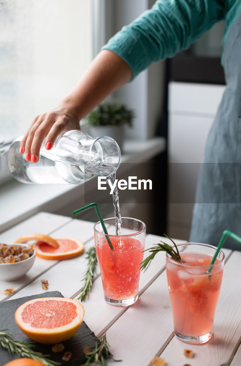 Woman preparing lemonade at home. cooking in the kitchen. female hands. summer drink.