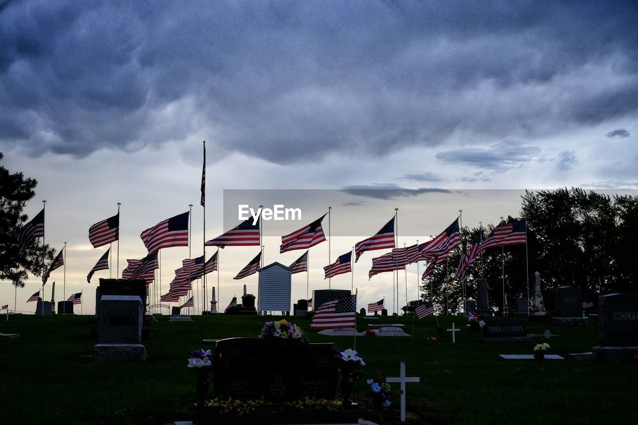 cemetery, cloud - sky, memorial, flag, in a row, sky, large group of people, ceremony, patriotism, outdoors, army soldier, tree, grass, military, day, nature, people