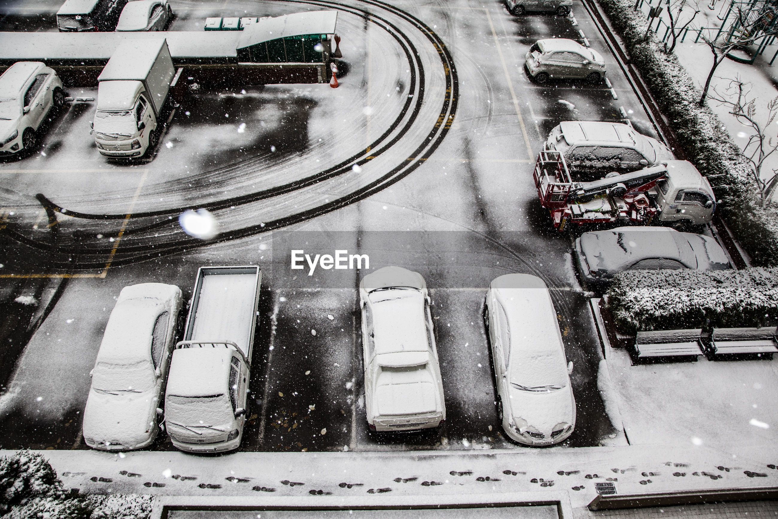 High angle view of snow covered vehicles parked at parking lot