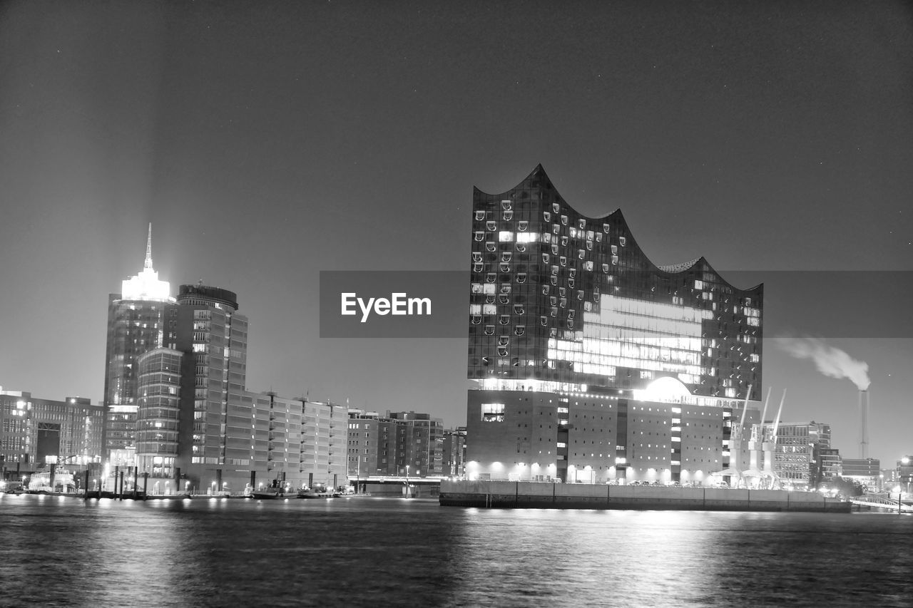 architecture, built structure, building exterior, building, illuminated, city, water, sky, waterfront, office building exterior, night, skyscraper, river, nature, no people, modern, travel destinations, cityscape, urban skyline, tall - high, outdoors, financial district