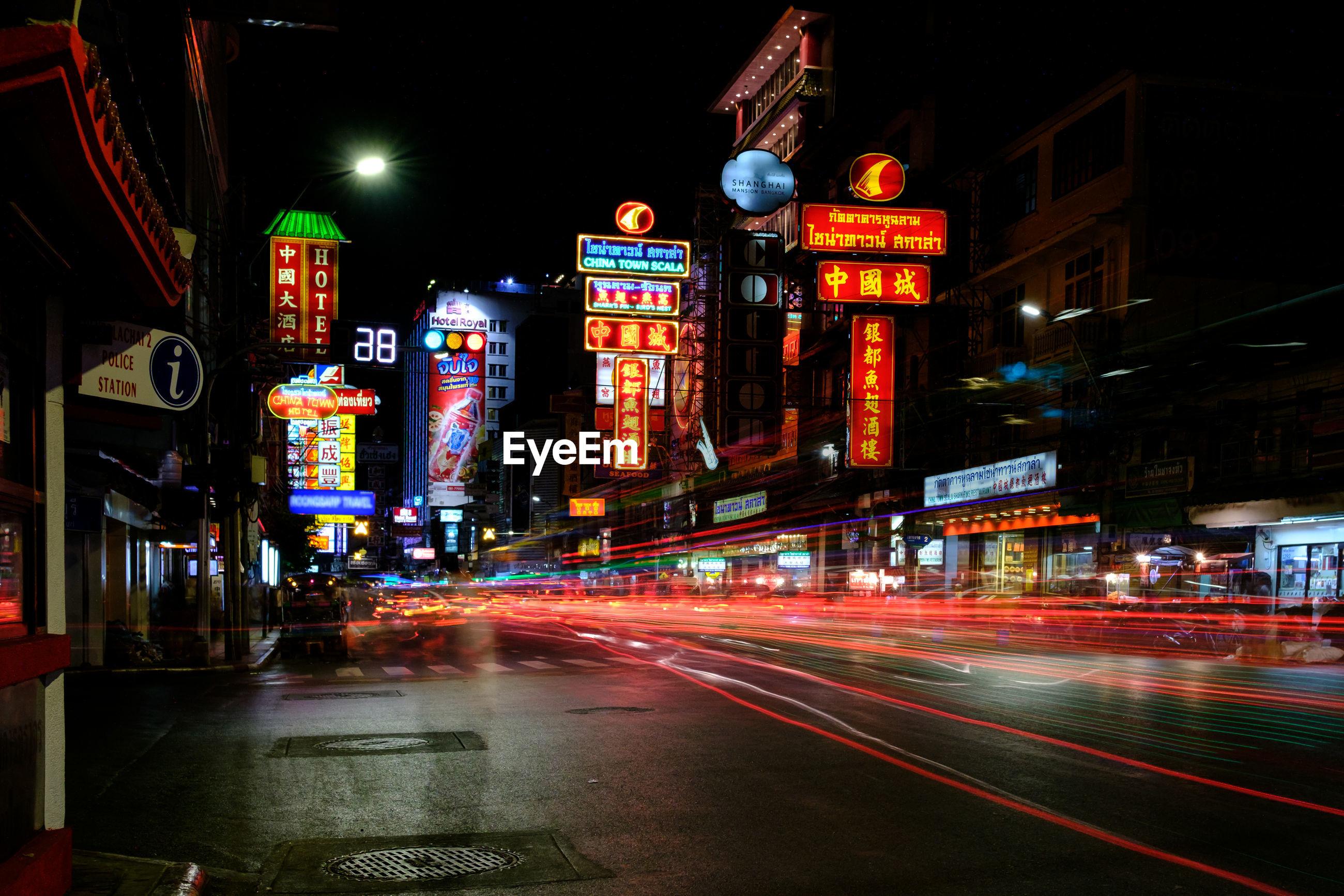 LIGHT TRAILS ON CITY STREET AGAINST ILLUMINATED BUILDINGS AT NIGHT