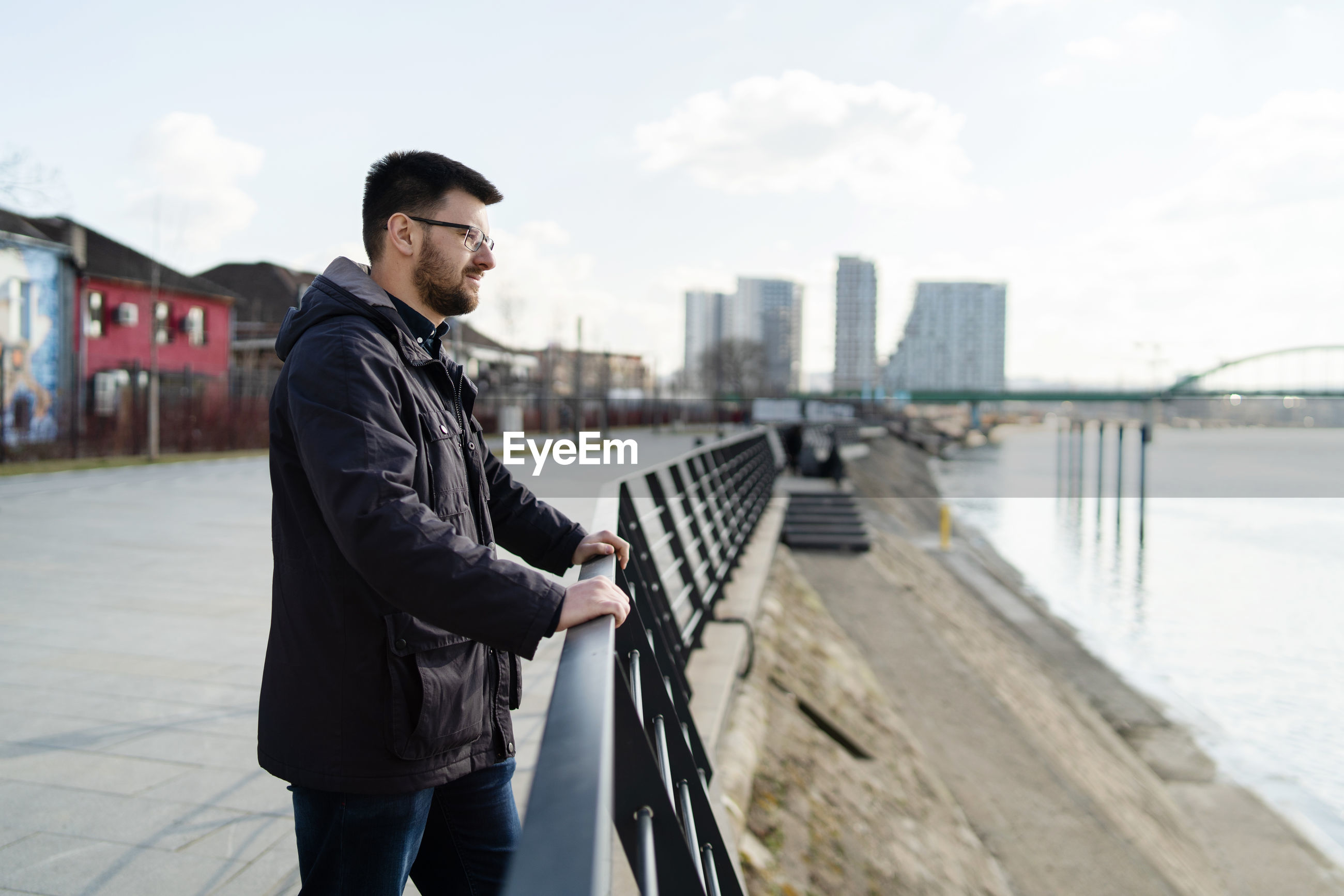 Man standing on railing in city against sky