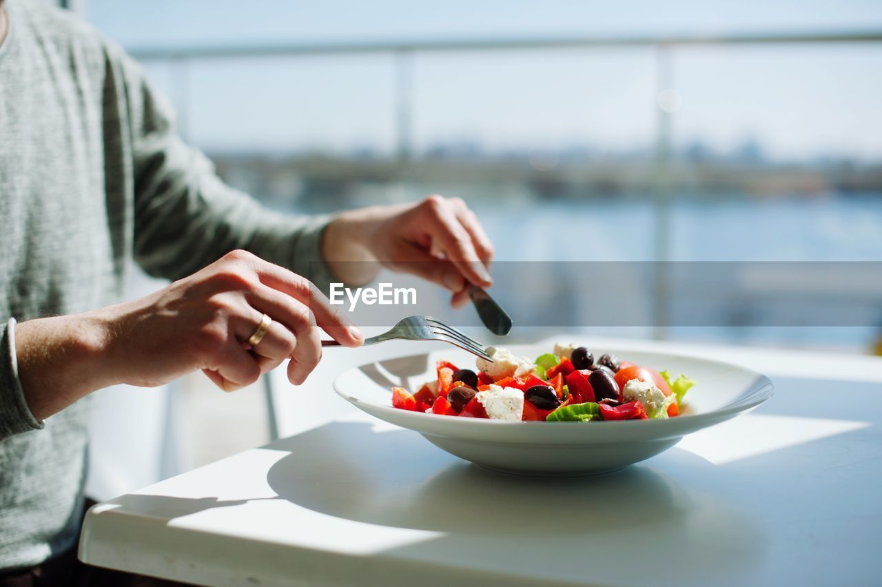 Midsection of man preparing food in bowl on table
