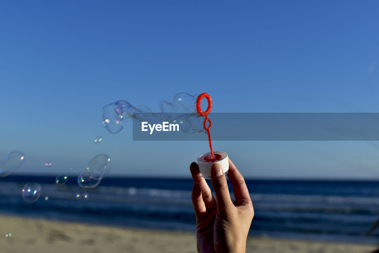 Hand holding bubble wand at beach