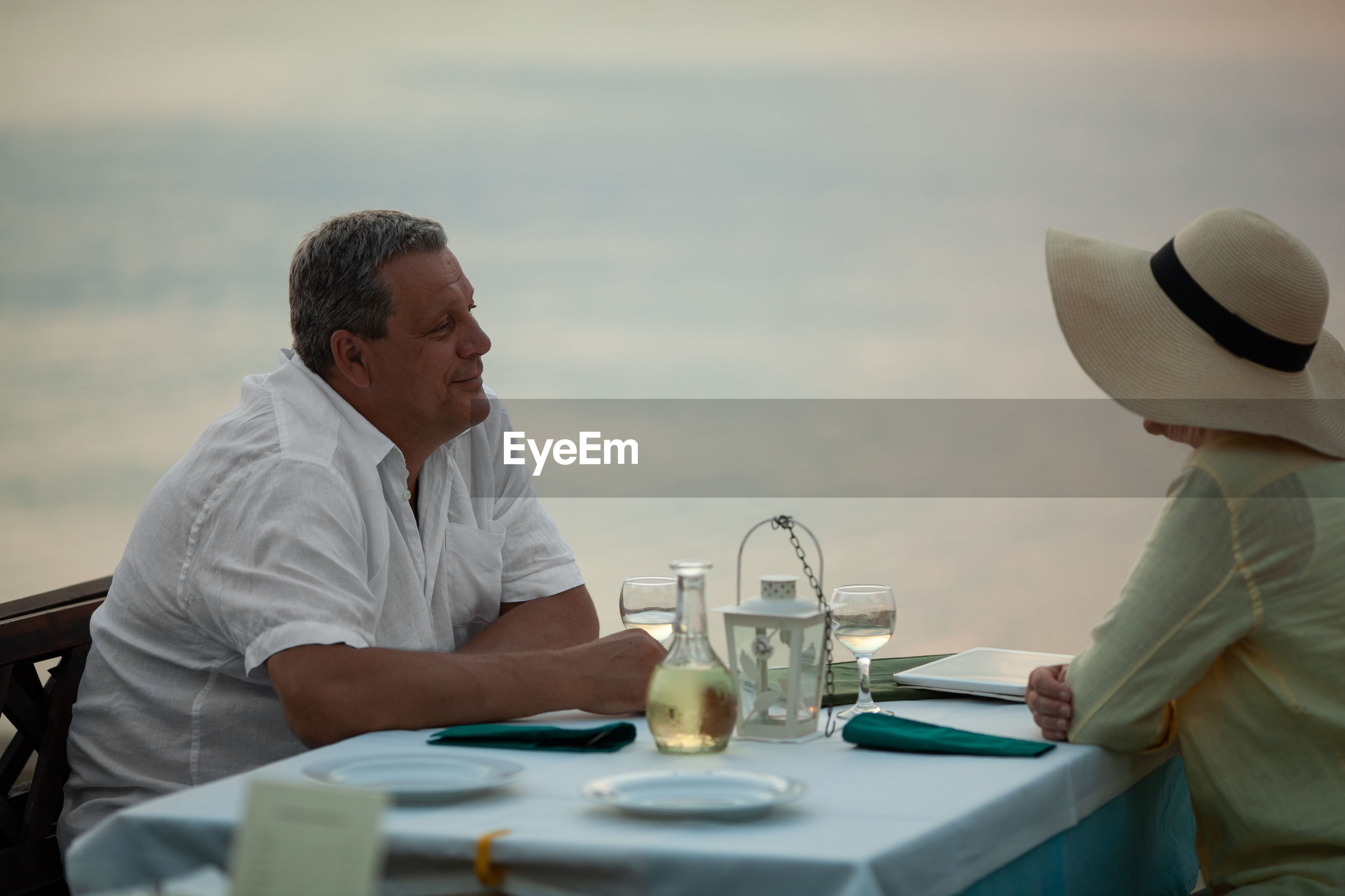 Mature couple sitting at restaurant table against sea