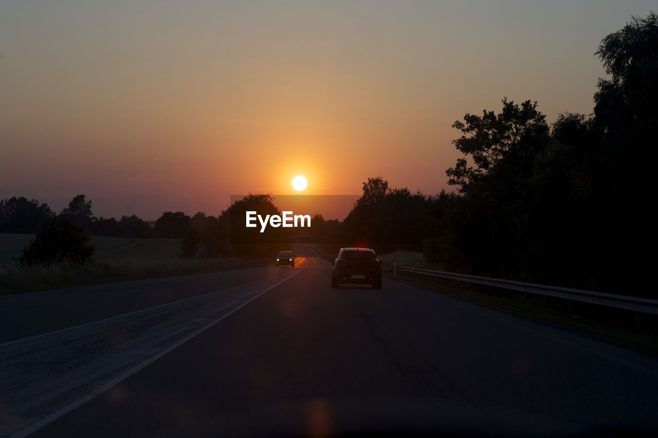 CAR ON COUNTRY ROAD AGAINST CLEAR SKY AT SUNSET