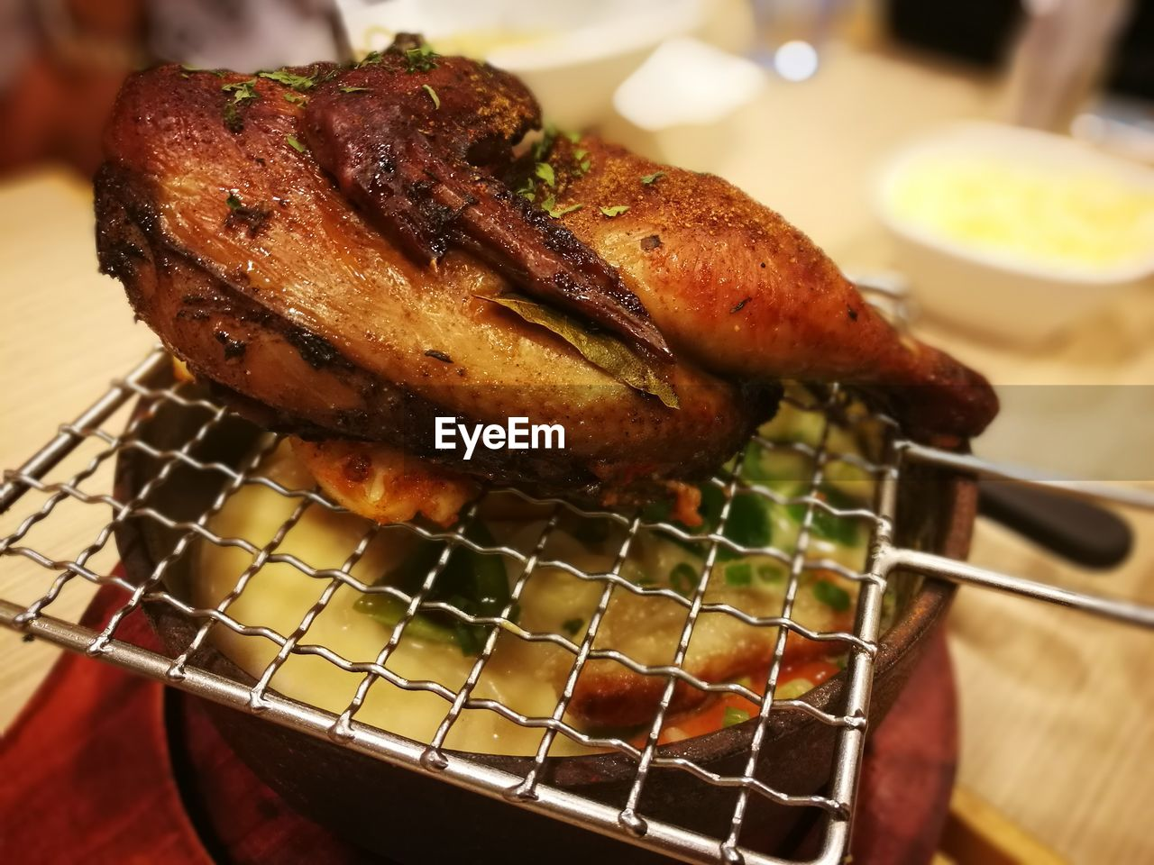 Roast Chicken On Metal Grate Over Earthen Hot Pot On Table