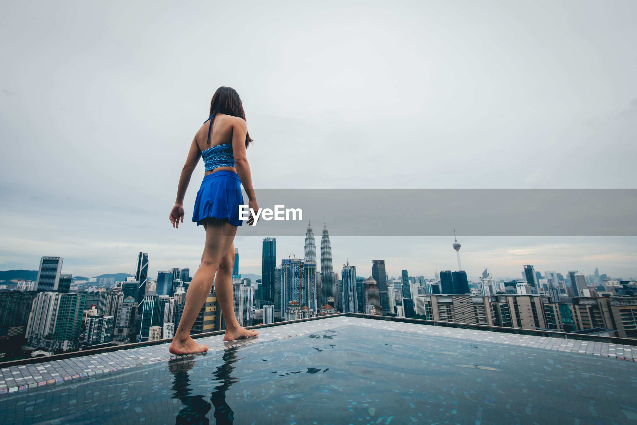 Rear view of woman standing by swimming pool against buildings in city