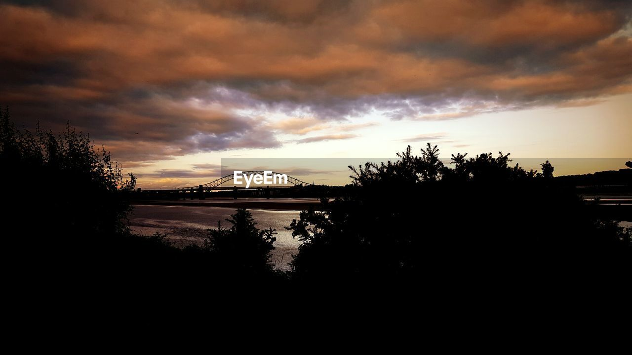 cloud - sky, sunset, sky, water, river, silhouette, dramatic sky, nature, bridge - man made structure, scenics, dusk, built structure, no people, beauty in nature, tree, tranquil scene, outdoors, tranquility, architecture, travel destinations, day