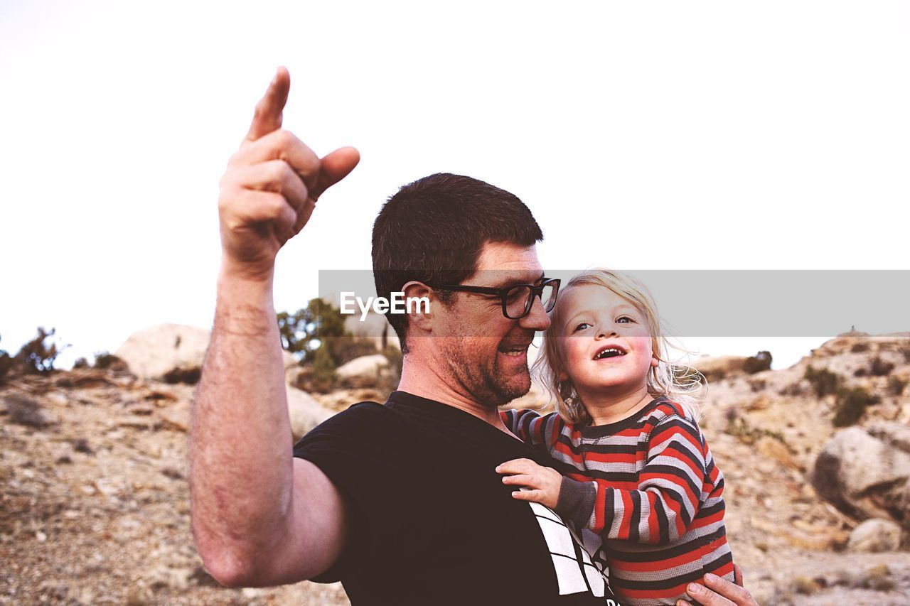 Happy Father Pointing While Carrying Son Against Clear Sky