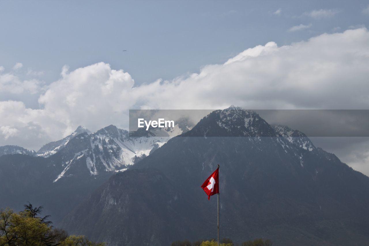 Switzerland flag against rocky mountains