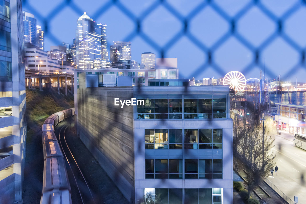 Illuminated buildings in city seen through chainlink fence at dusk