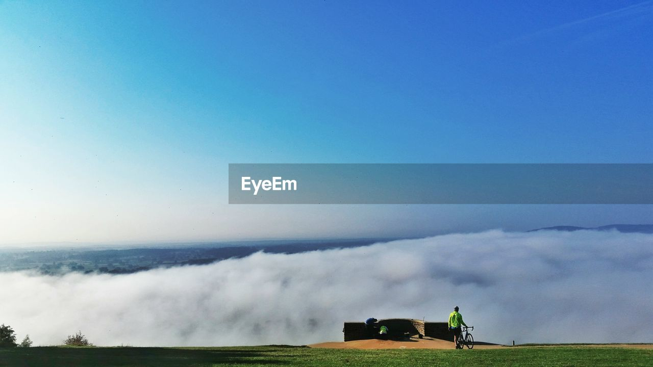 Man With Bicycle On Cliff Against Cloudscape