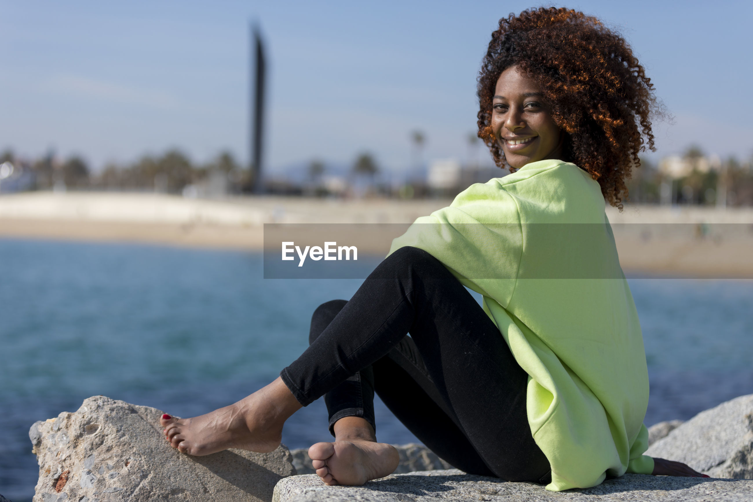 Portrait of young woman sitting outdoors on rock by sea