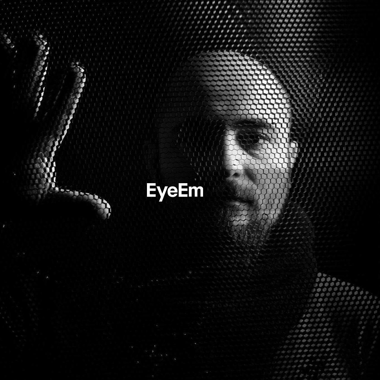 Portrait Of Man Seen Through Fence In Darkroom