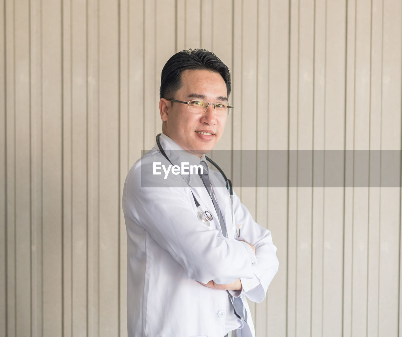 Portrait Of Smiling Doctor Standing Against Wall