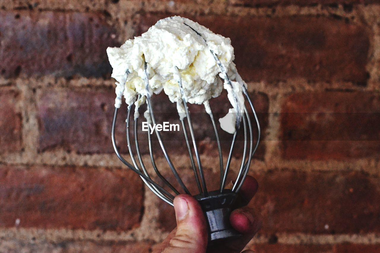 Cropped hand holding beaten egg whites on whisk