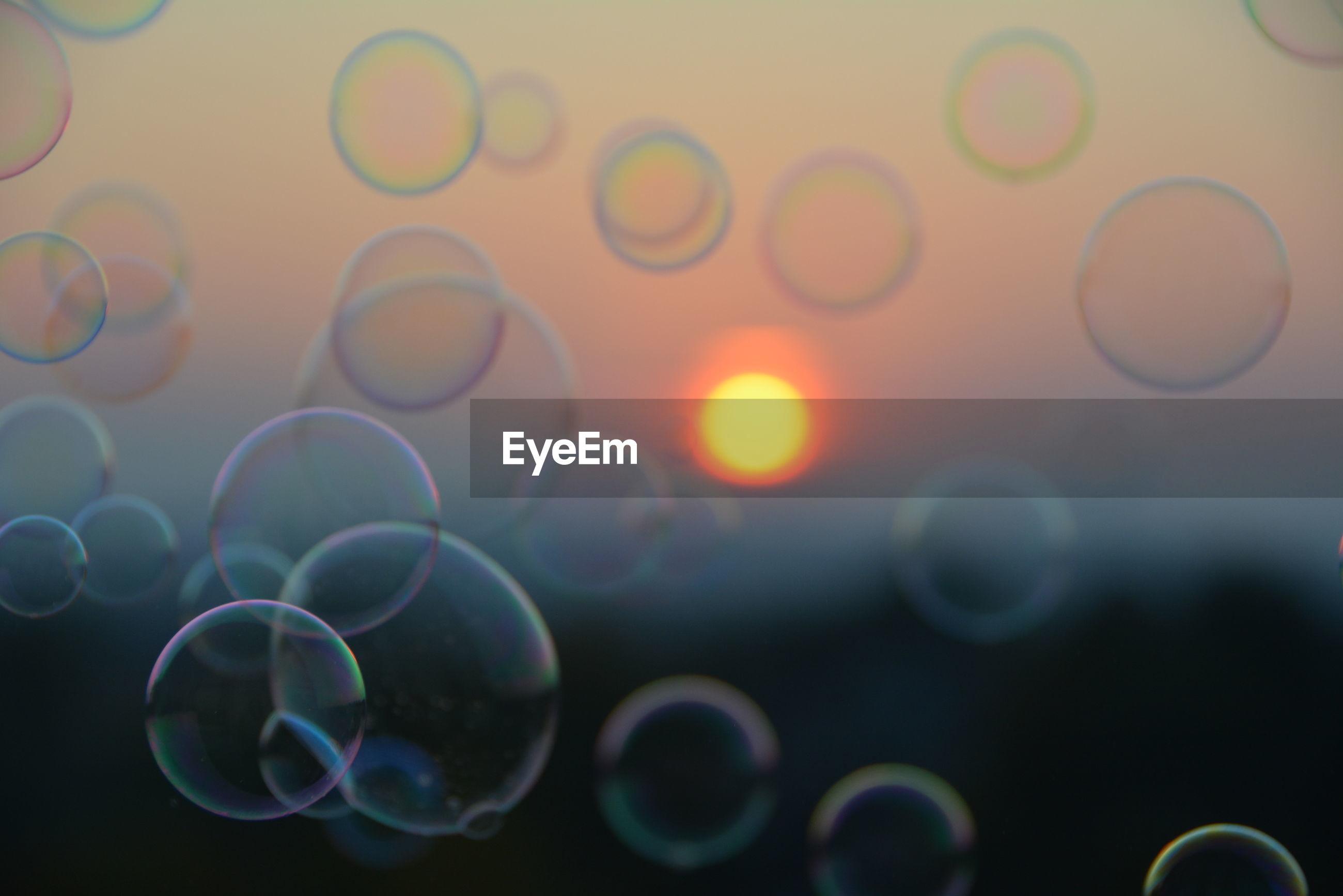 Bubbles in mid-air against orange sun