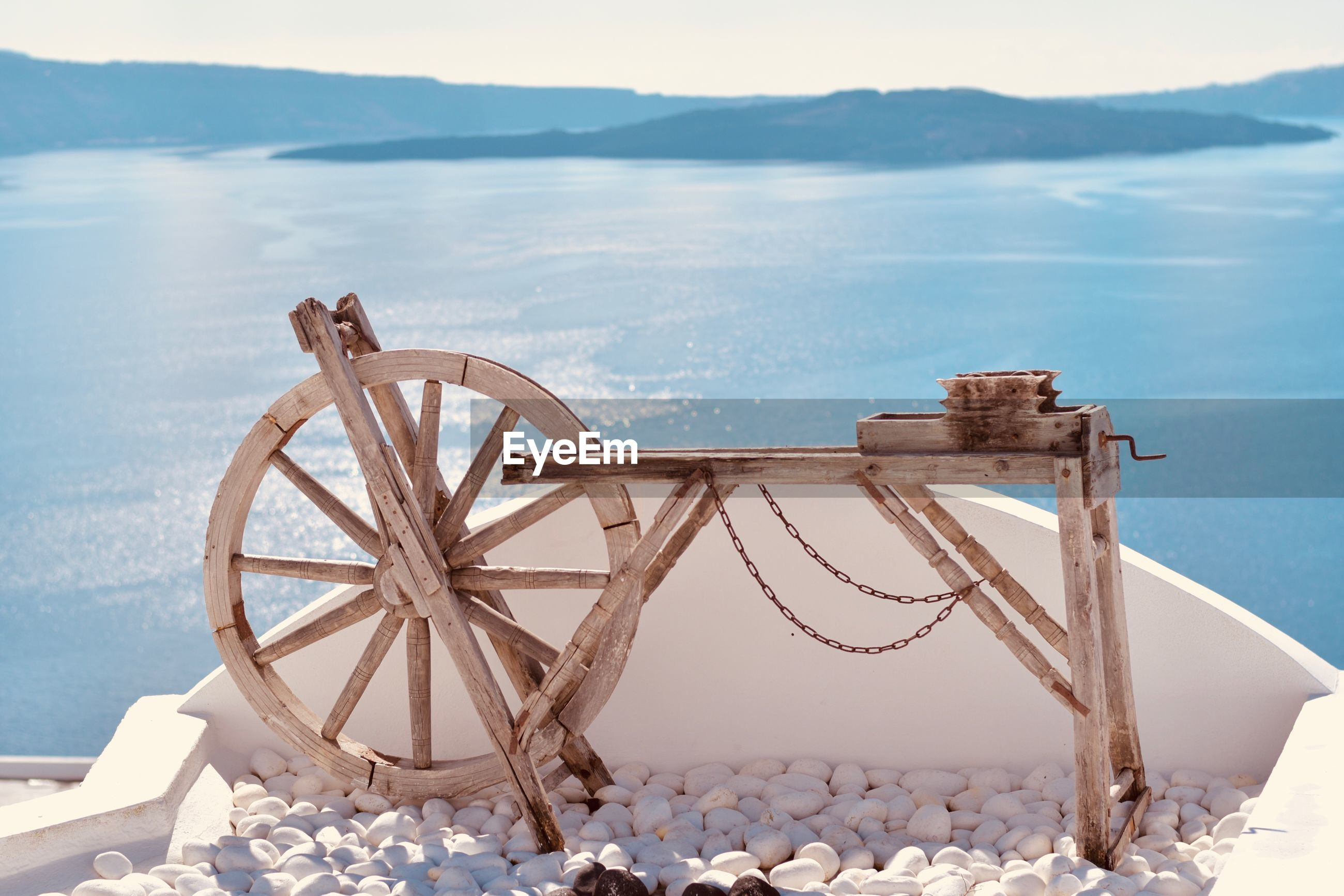 Wooden spinning wheel on pebbles against sea