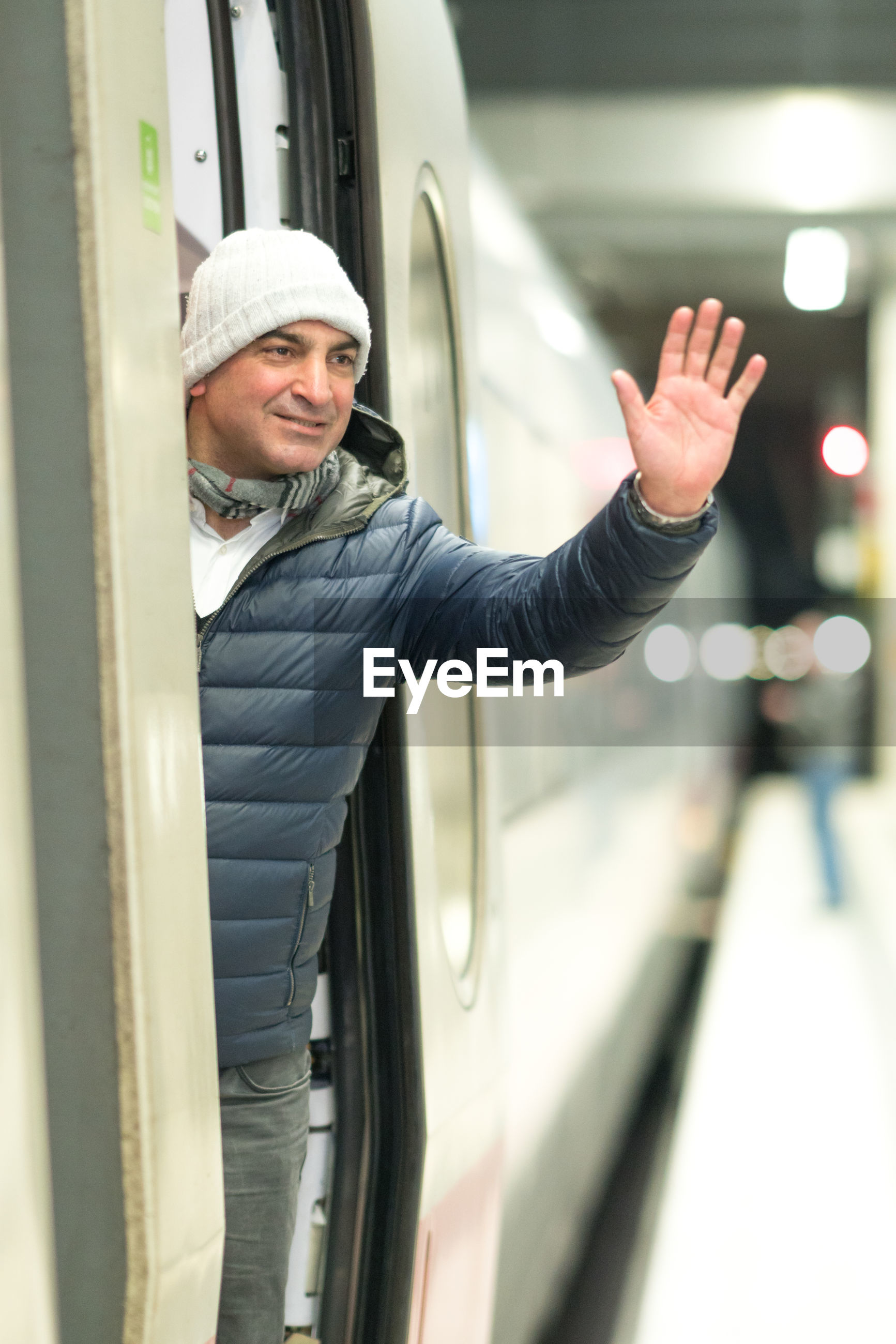 Man waving hand while standing in train