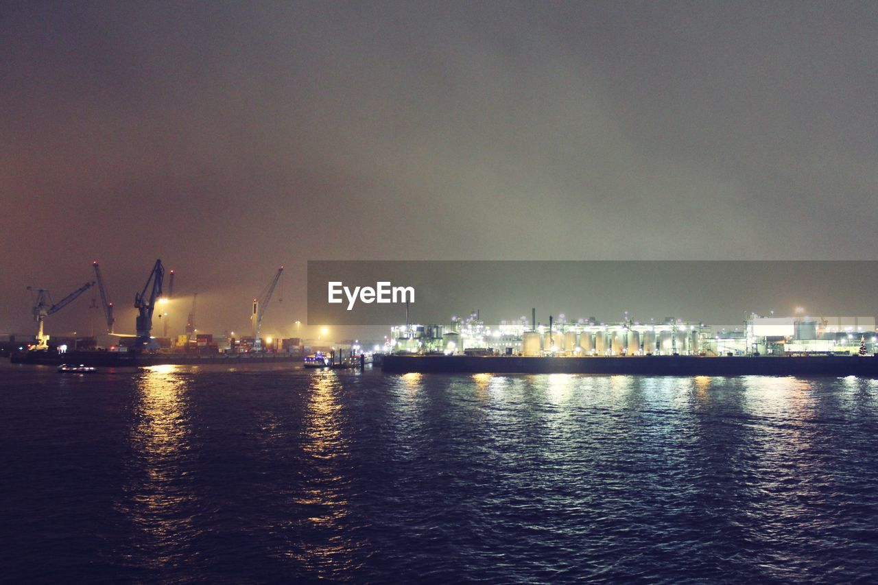 waterfront, sky, night, water, illuminated, sea, cloud - sky, built structure, architecture, building exterior, no people, crane, reflection, crane - construction machinery, outdoors, city, industry, skyscraper, travel destinations, nautical vessel, nature, cityscape, urban skyline