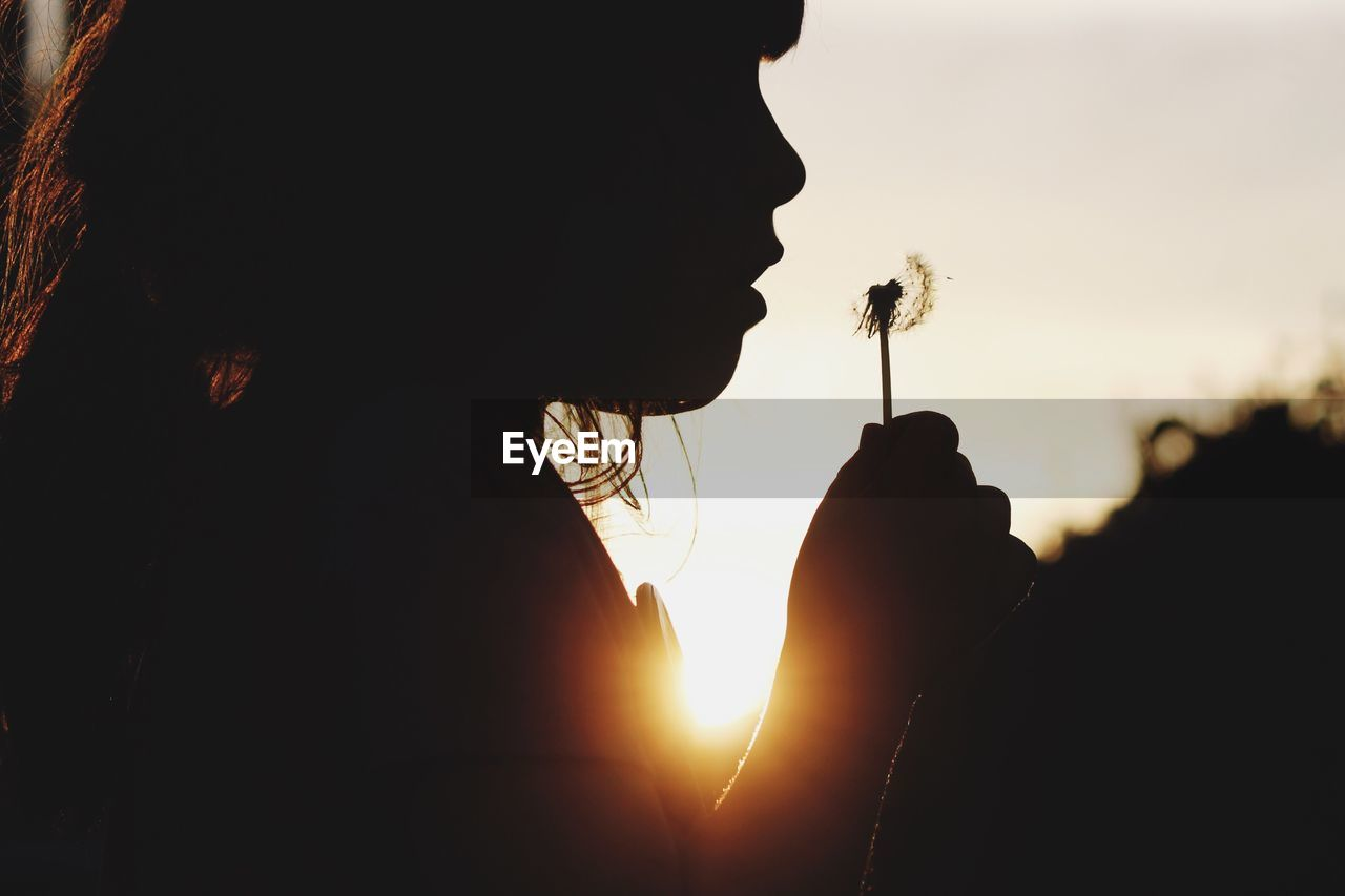 Silhouette of girl blowing dandelion flower against sky during sunset