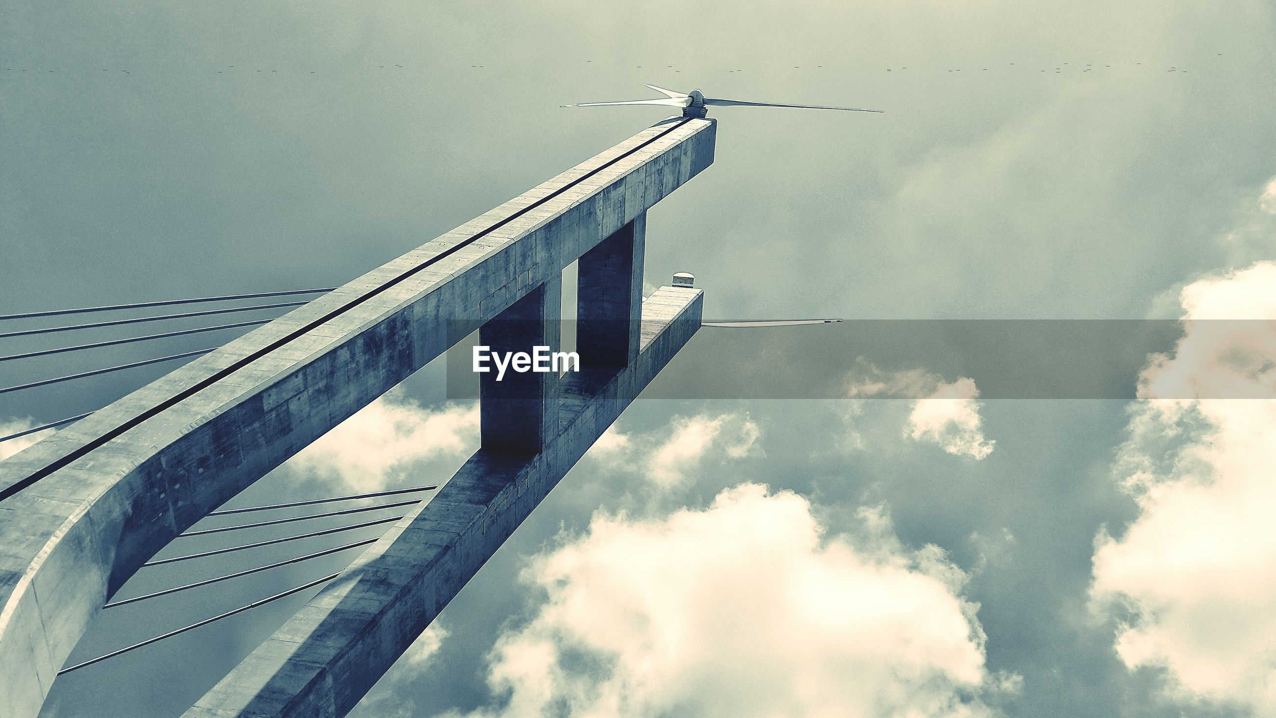 LOW ANGLE VIEW OF BRIDGE IN CITY AGAINST SKY