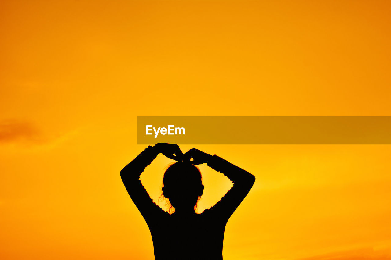 Silhouette Woman Standing Against Orange Sky