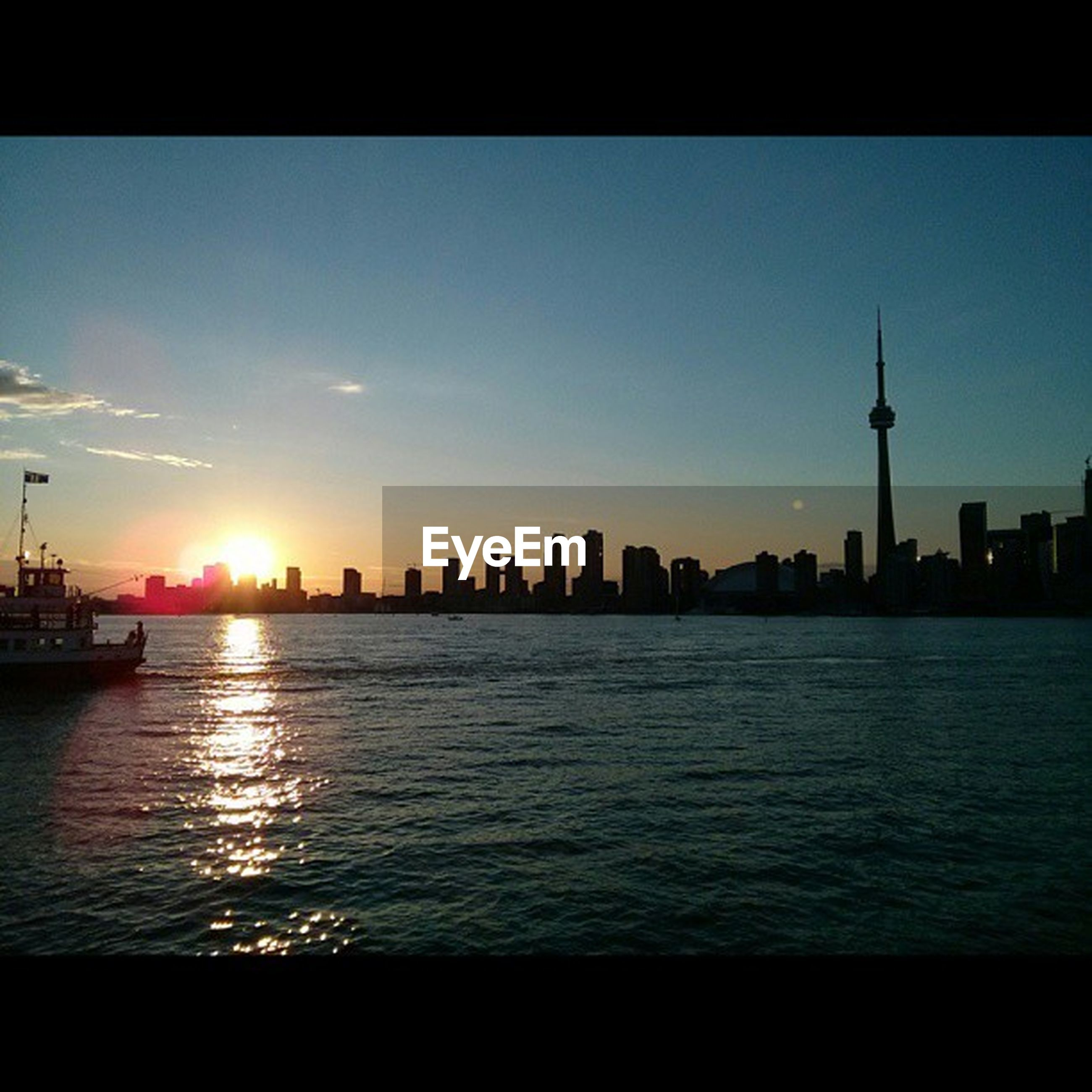 sunset, building exterior, architecture, water, built structure, city, tower, silhouette, sea, cityscape, sky, waterfront, urban skyline, skyscraper, river, tall - high, sun, communications tower, travel destinations, skyline