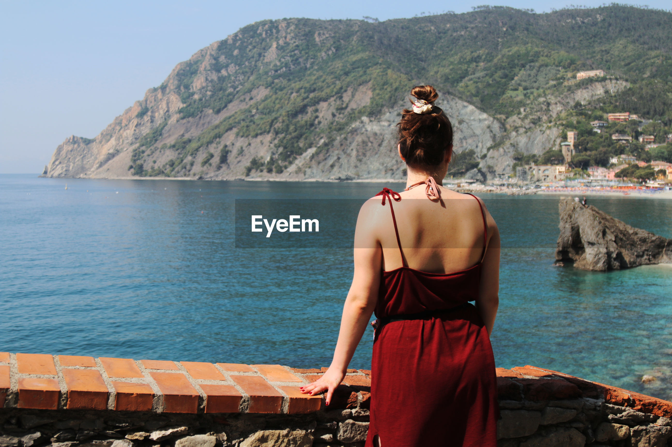 Rear view of woman wearing red dress while standing by retaining wall against sea