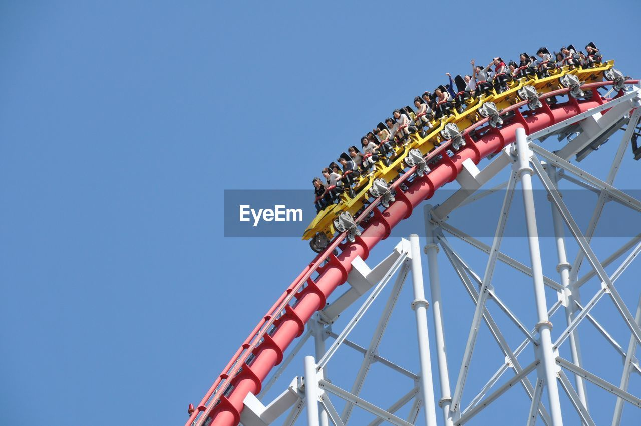 Low Angle View Of Roller Coaster Against Clear Blue Sky