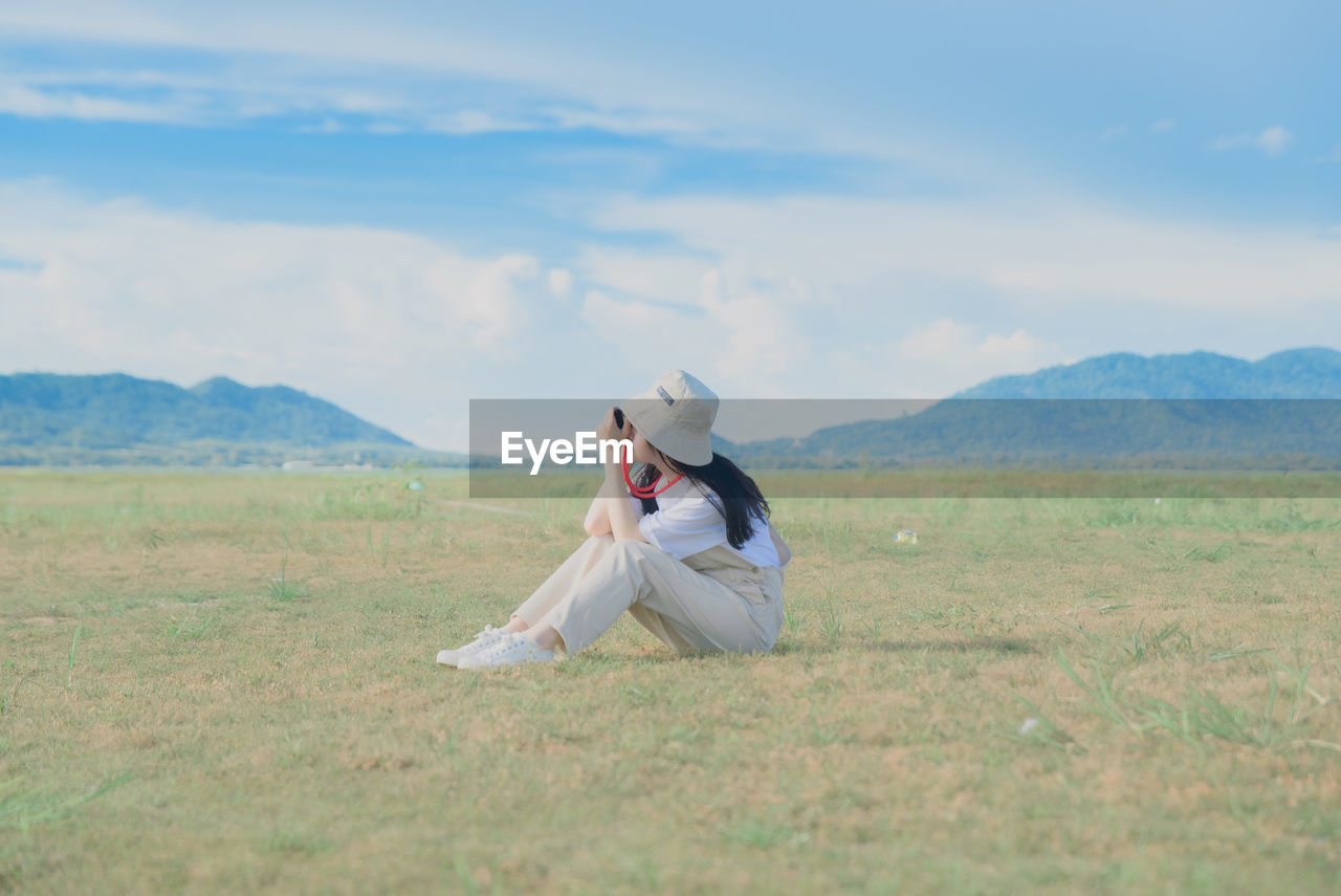 Full length of woman sitting on field against sky