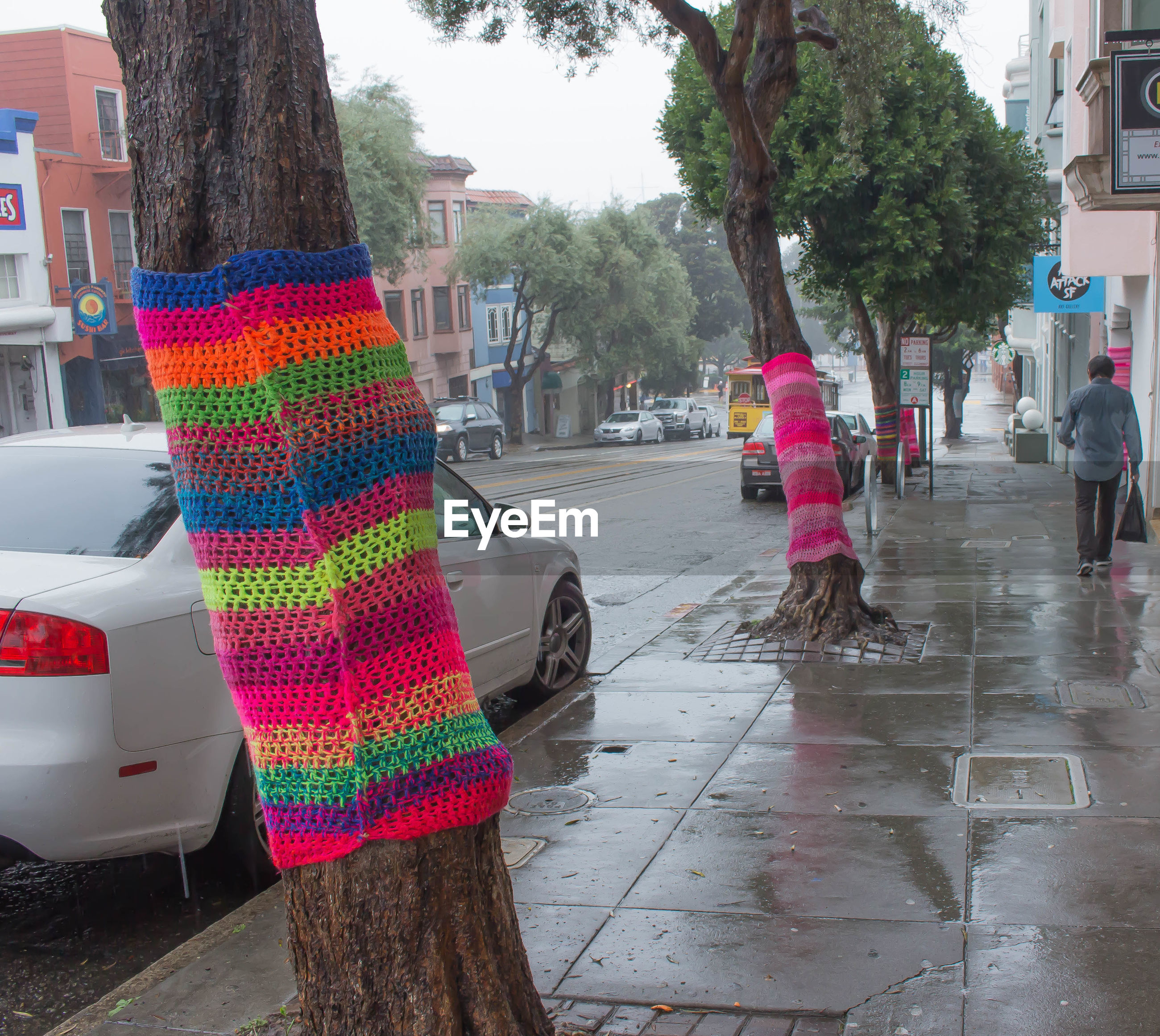 Multi colored fabric decoration on trees at sidewalk in city