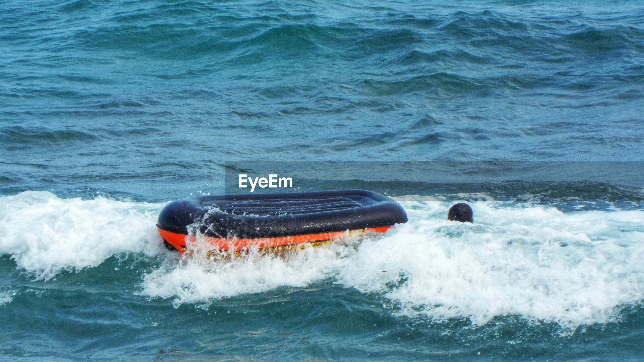 Person with sea with overturned boat