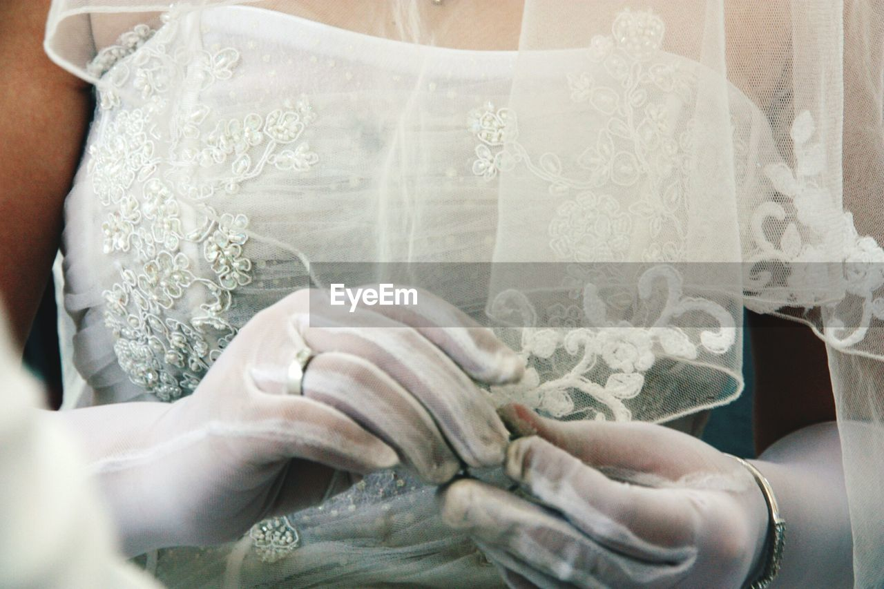 Midsection Of Bride Holding Wedding Ring