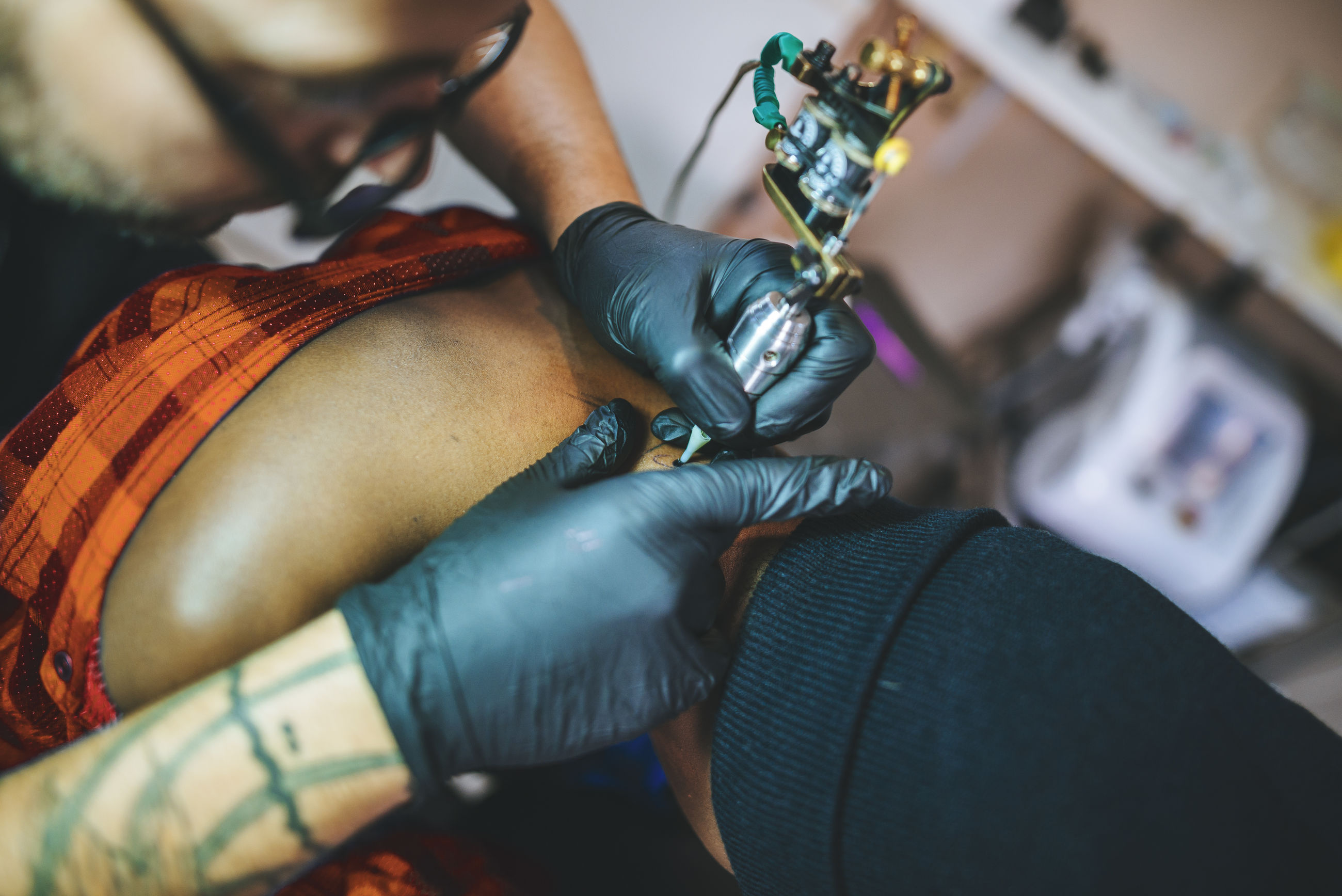 High angle view of artist drawing tattoo on young woman in studio