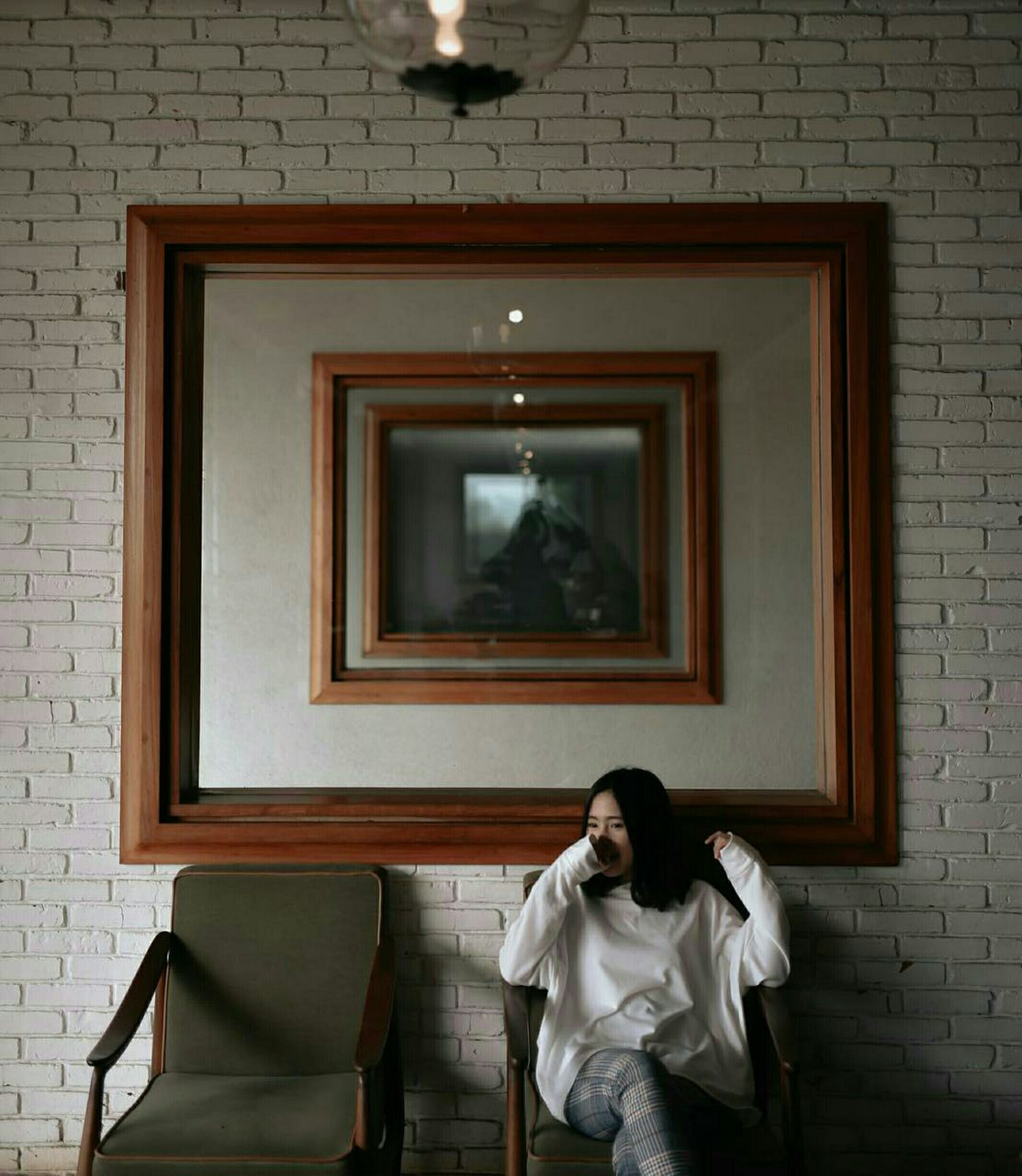 Woman Sitting On Chair Against Picture Frame