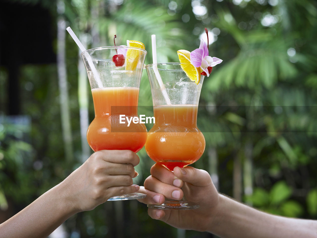 Cropped hands toasting drinks outdoors