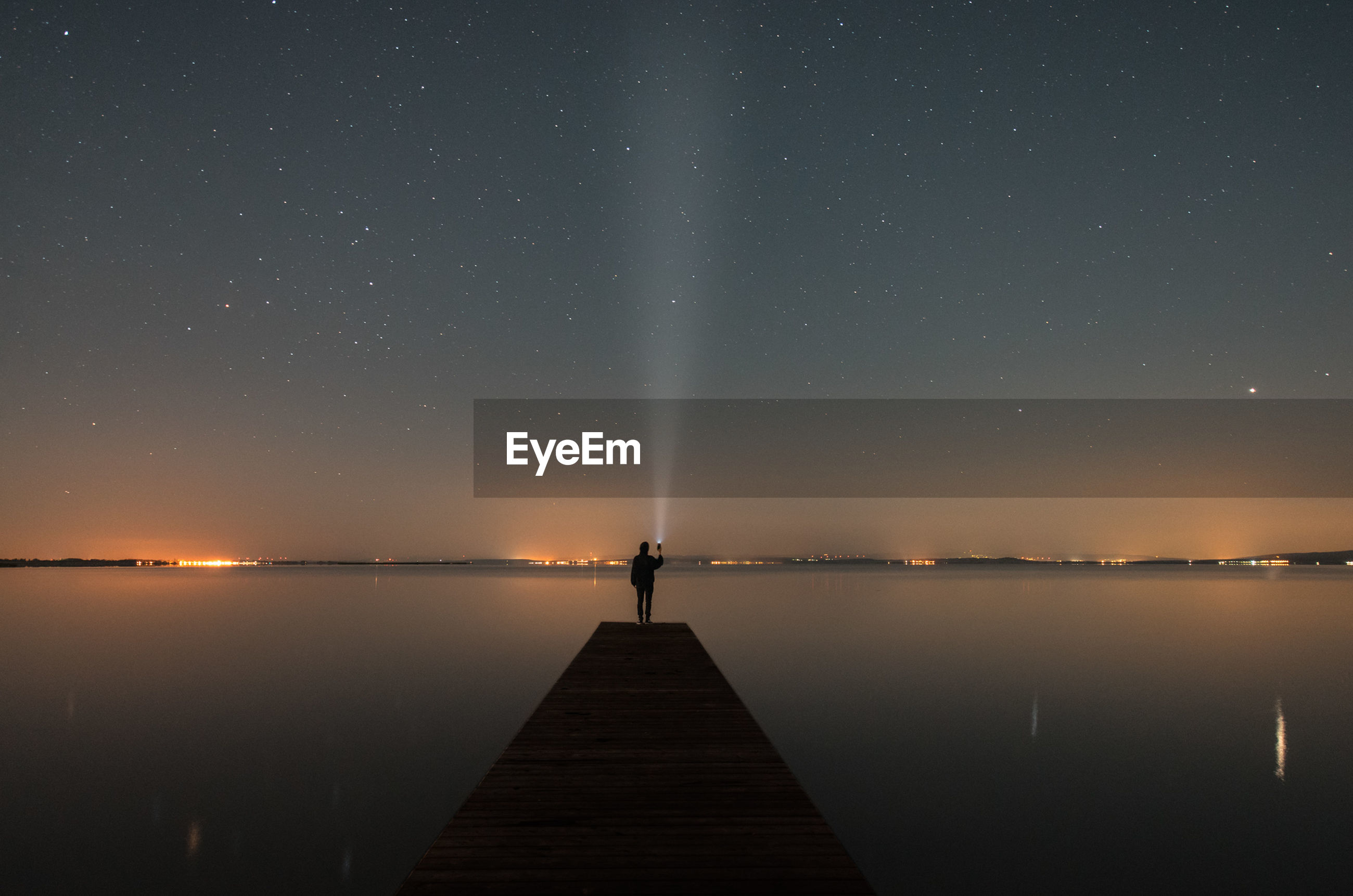 Man standing on pier over lake against sky at night