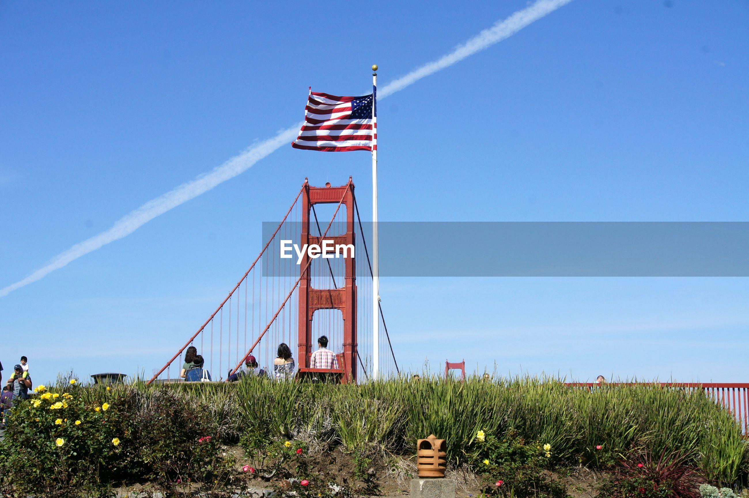 Golden gate bridge and american flag against blue sky