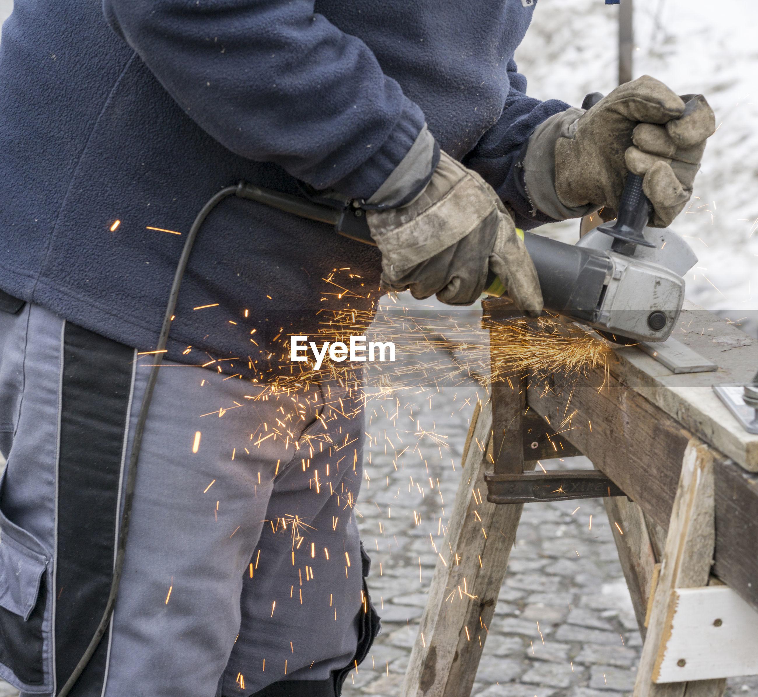 Midsection of man grinding metal at workshop