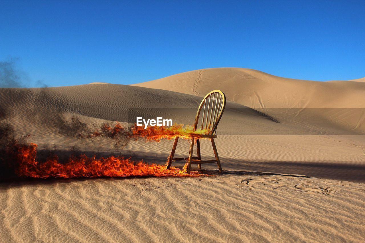 Burning Chair In Desert Against Clear Blue Sky