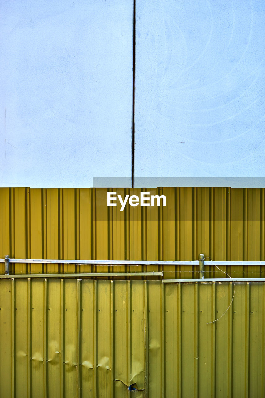 yellow, architecture, metal, no people, built structure, wall - building feature, building exterior, day, blue, full frame, pattern, industry, backgrounds, outdoors, building, textured, protection, factory, copy space, close-up, iron, corrugated