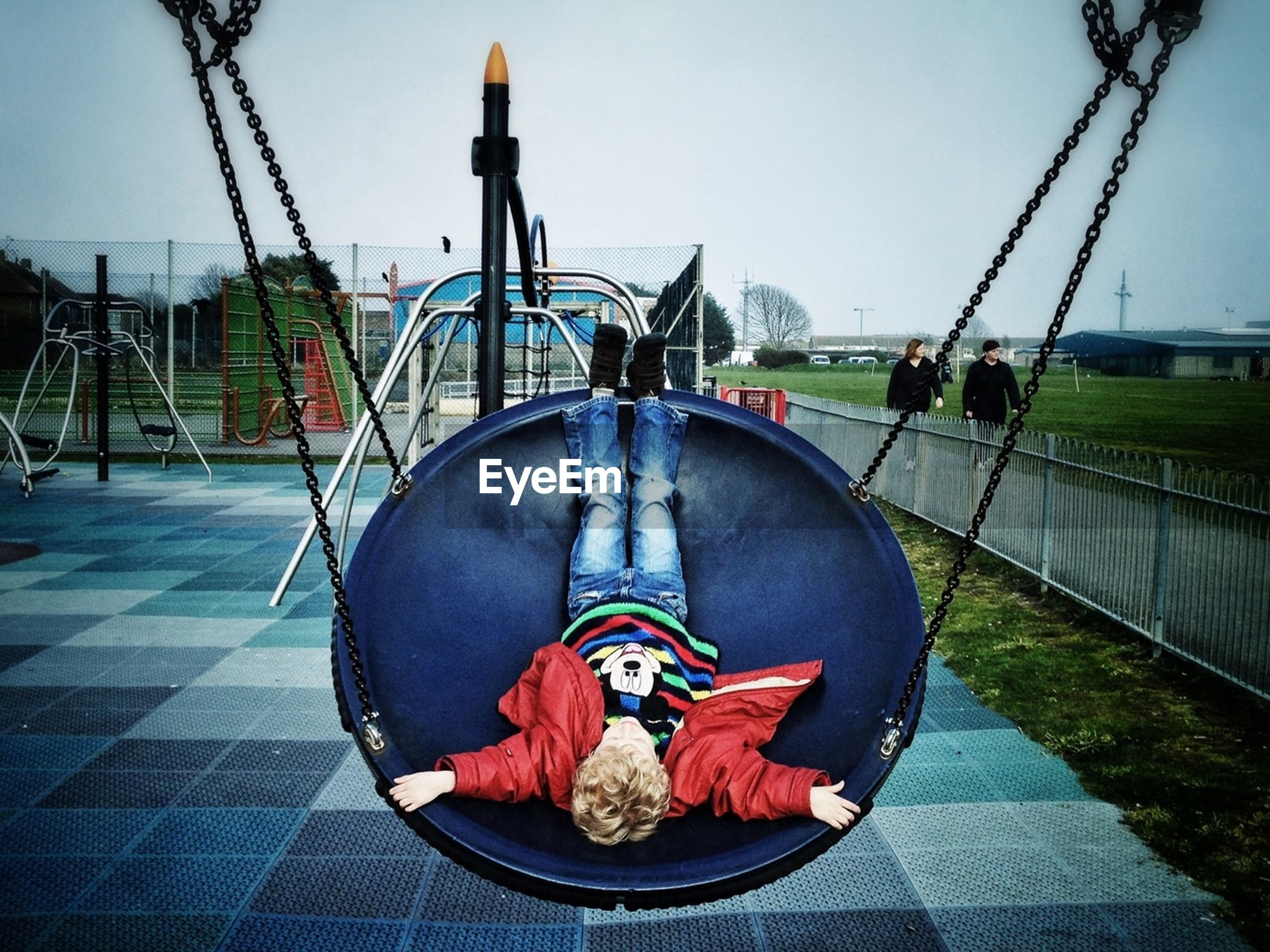 UPSIDE DOWN IMAGE OF GIRL RELAXING ON FOOTPATH AT PARK AGAINST CLEAR SKY