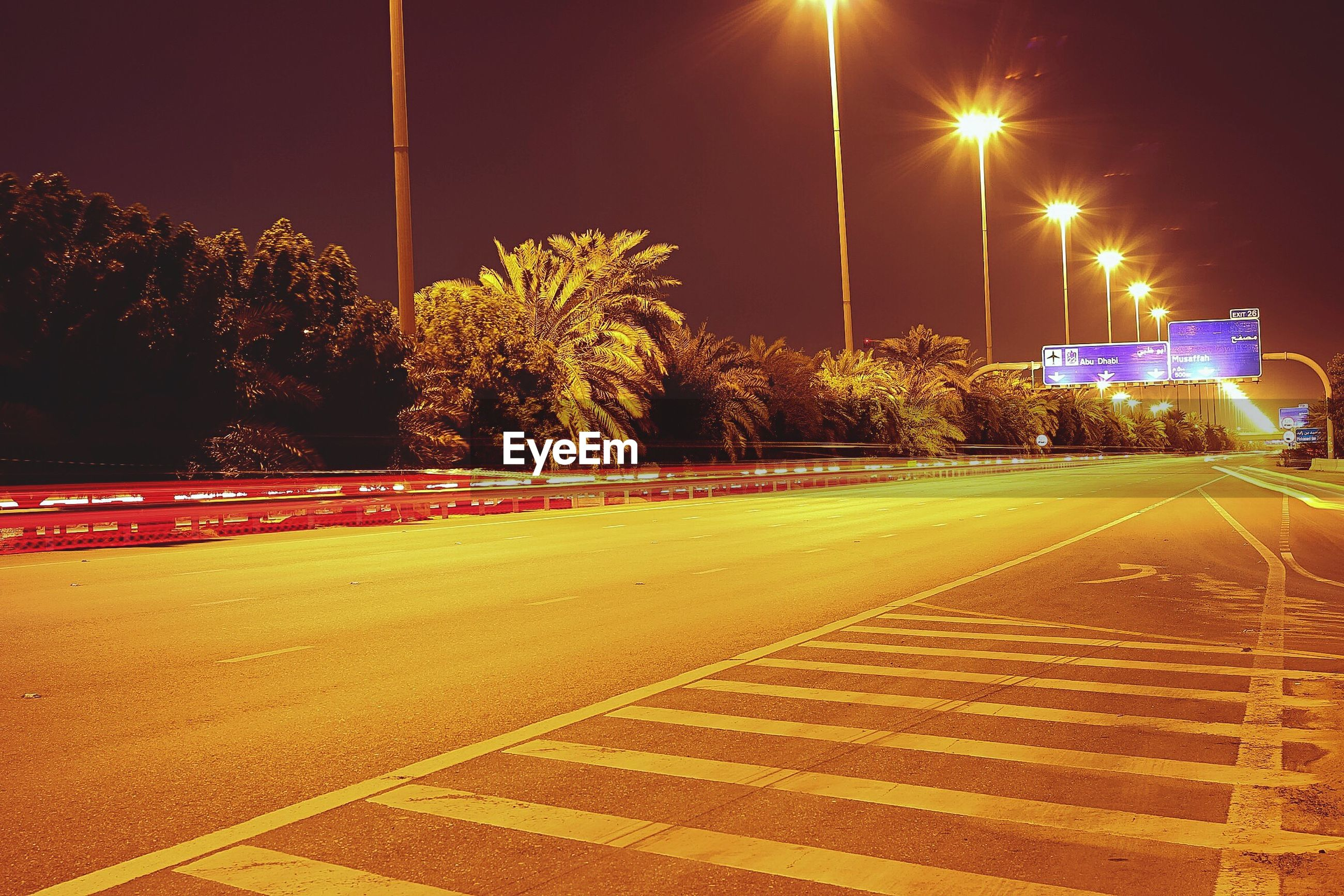 Surface level of empty road along lit street lights