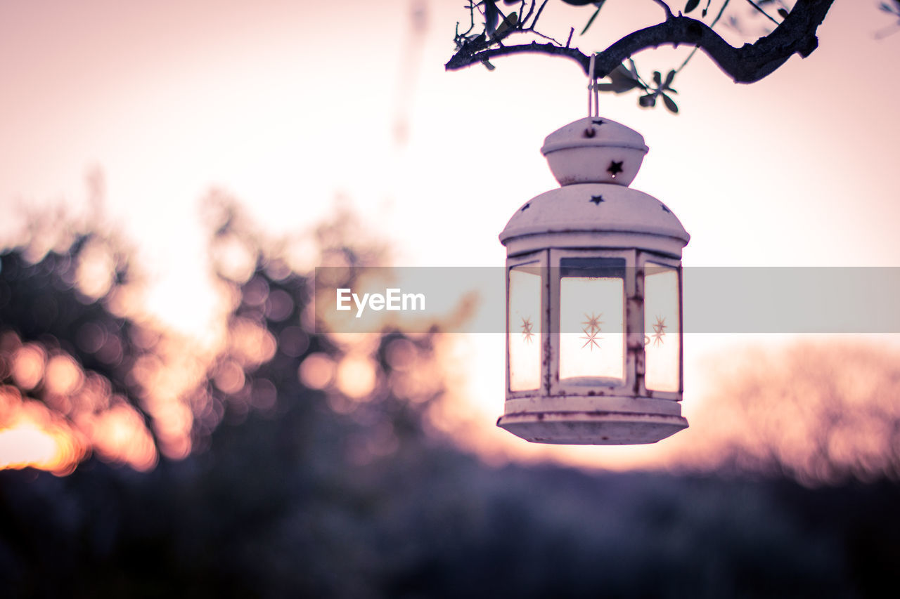 architecture, built structure, lighting equipment, building exterior, focus on foreground, sky, nature, no people, selective focus, low angle view, hanging, outdoors, tower, building, glass - material, close-up, day, sunset, old, clock