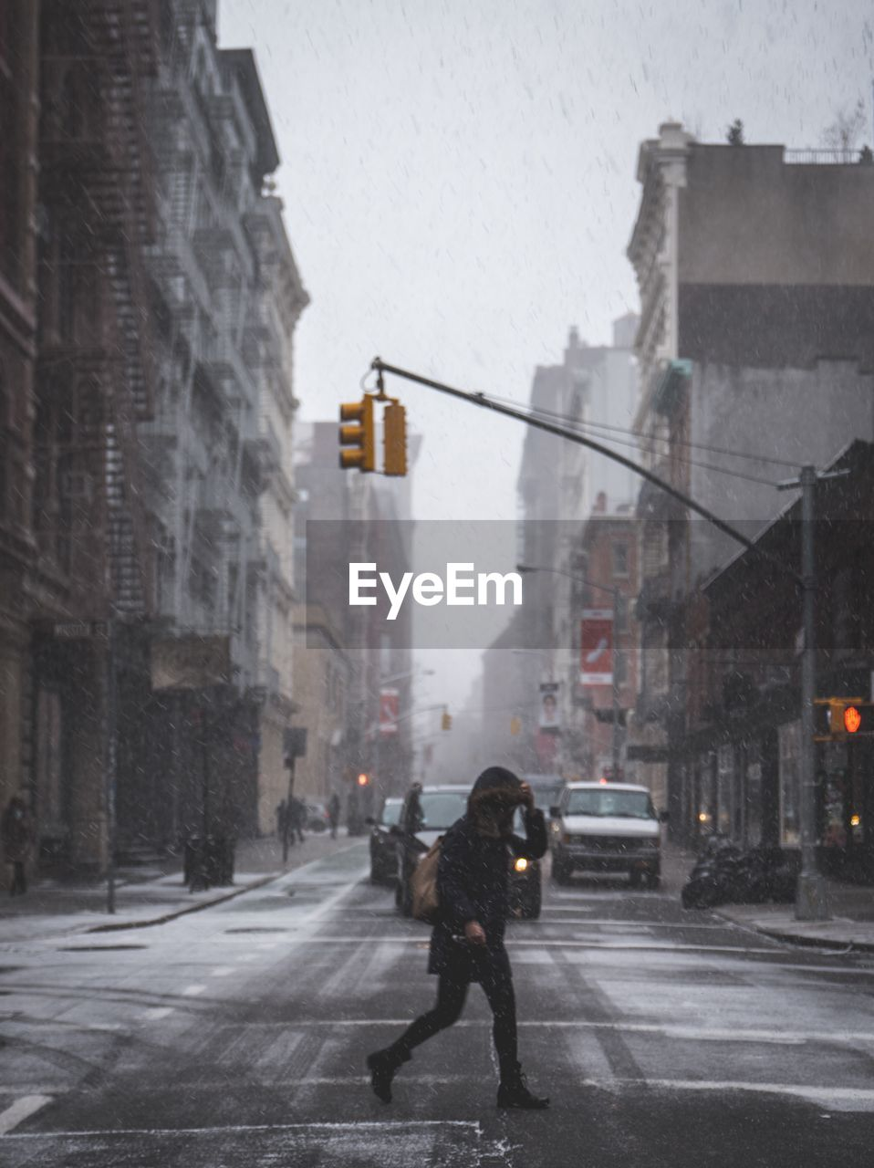 Full length side view of person crossing city street during snowfall