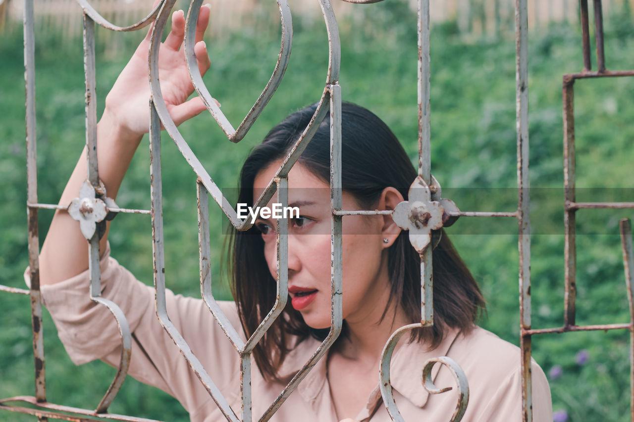 Woman looking away through railing