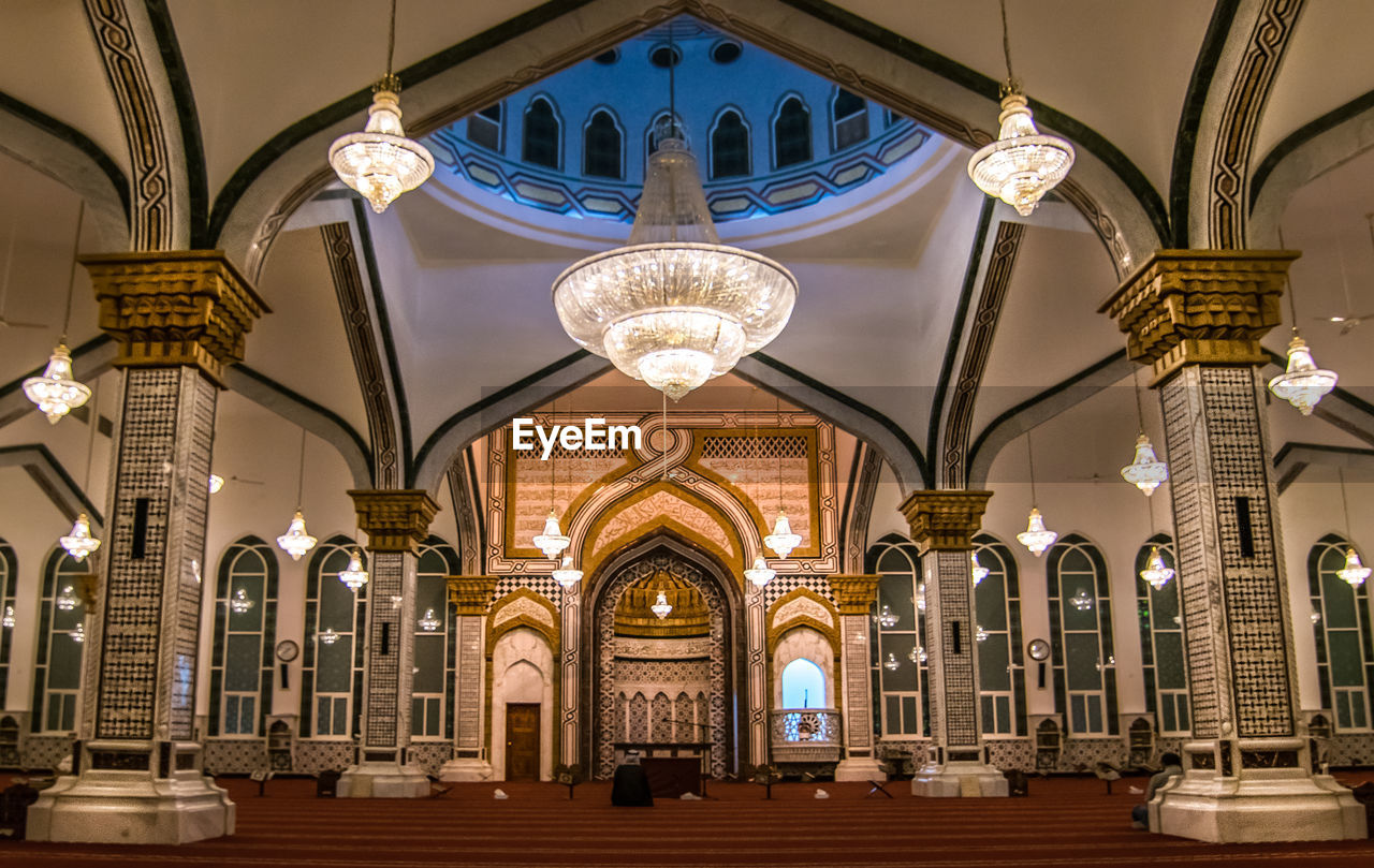 built structure, architecture, illuminated, lighting equipment, arch, architectural column, ceiling, building, indoors, belief, spirituality, no people, religion, hanging, low angle view, in a row, place of worship, chandelier, travel destinations, day, ornate, luxury, light, architecture and art